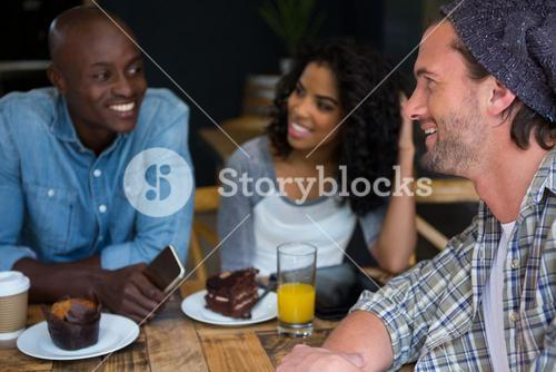 Man talking with friends at table in coffee house