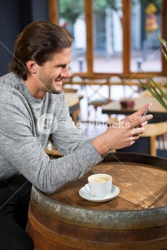 Man using smart phone at table in coffee shop