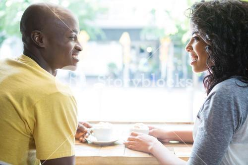 Couple looking at each other at table in coffee house