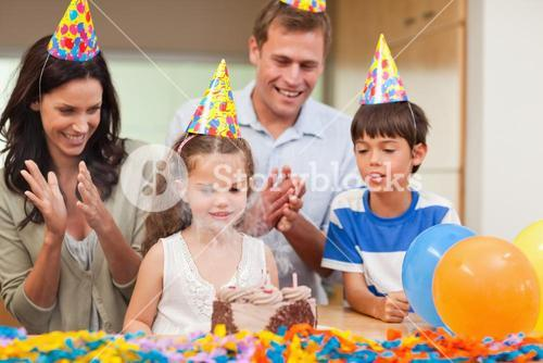 Parents applauding her daughter who just blew out the candles on birthday cake