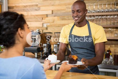 Male barista serving coffee and dessert to female customer