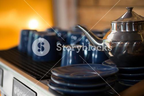 Kettle with cups and saucers in coffee shop
