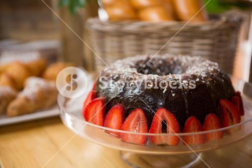 Bundt cake surrounded by strawberries in coffee house