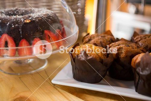 Muffins and cake on counter in coffee shop