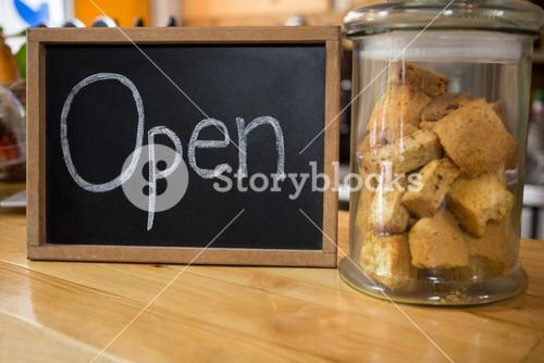Open sign by cookies in jar on counter