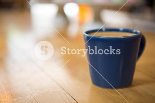 Coffee cup on wooden table in cafeteria