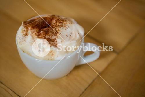 Coffee cup with creamy froth on table in cafe