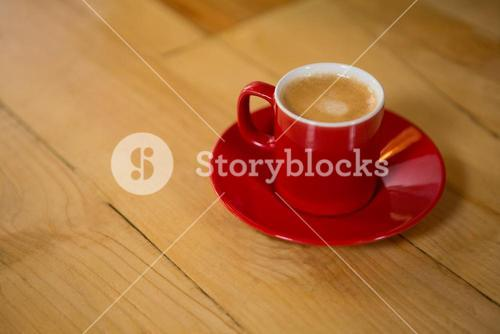 Red cup and saucer on table in coffee shop
