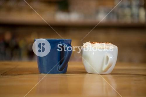 Coffee cups on wooden table in cafe