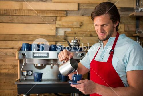 Barista pouring milk into cup at coffee shop