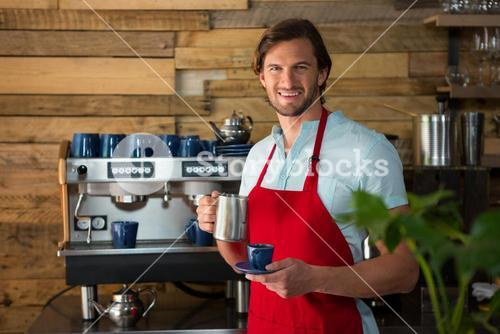 Smiling male barista making coffee in cafe