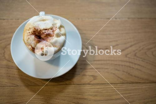 Coffee cup with creamy froth on table in cafeteria