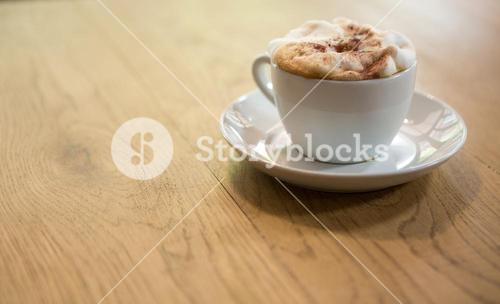 Coffee cup with creamy froth on table at cafe