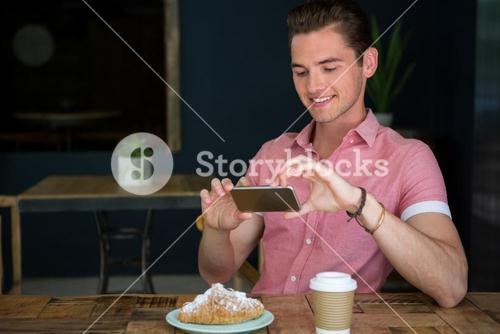 Man photographing food on table in coffee shop