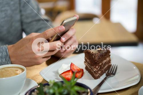 Man using mobile phone with coffee and dessert on table in cafe