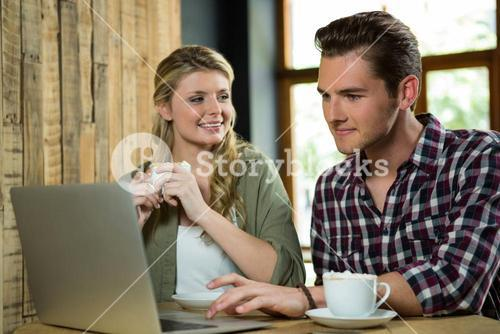 Woman looking at man using laptop in coffee shop