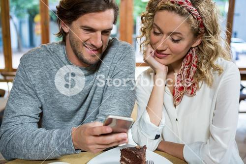 Smiling couple using smart phone at table in cafe
