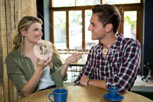 Happy woman talking with man at table in coffee shop