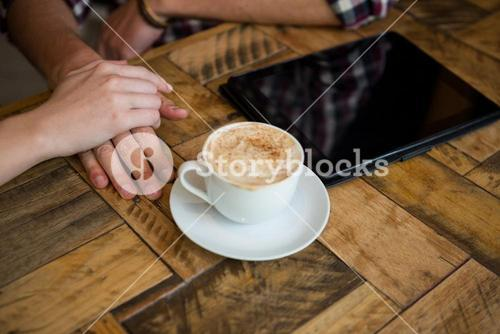 Couple holding hands with coffee cup and tablet PC on table in cafe