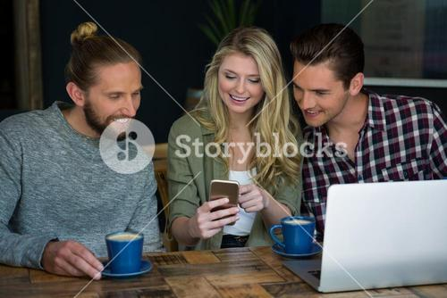 Smiling friends using smart phone at table in cafeteria