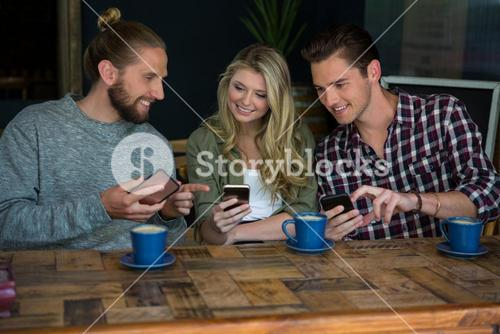 Smiling friends using smart phones at table in cafeteria
