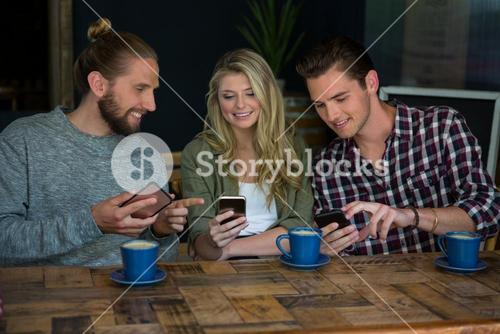 Smiling friends using smart phones at table in cafe