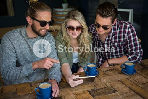 Smiling friends using smart phone at table in cafe