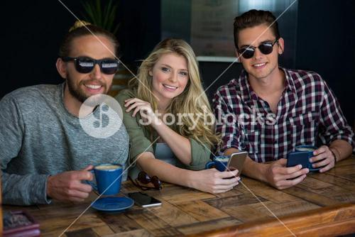 Woman with male friends wearing sunglasses in coffee shop