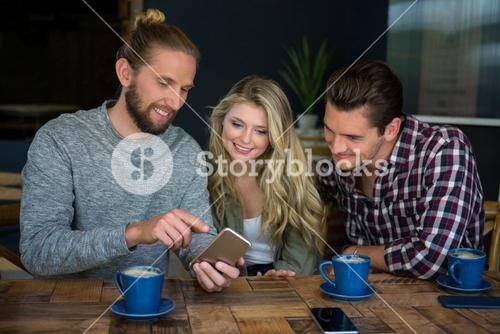 Man showing smart phone to friends at table in coffee shop