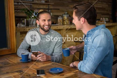 Smiling man talking with friend at table in coffee shop