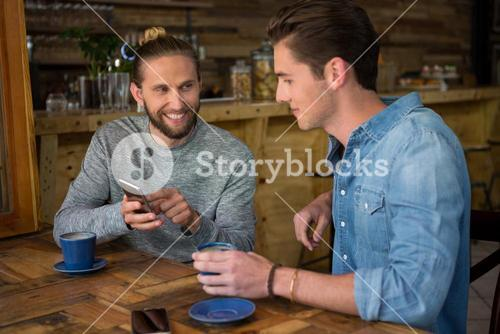 Happy man showing smart phone to friend in coffee shop