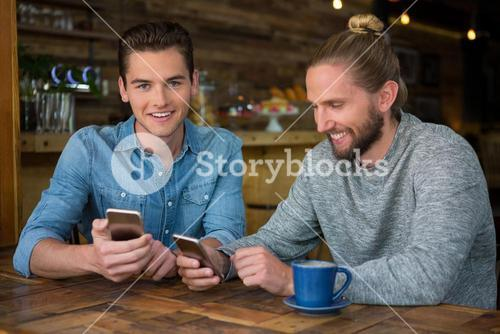 Smiling male hipsters using smart phones at table in coffee shop