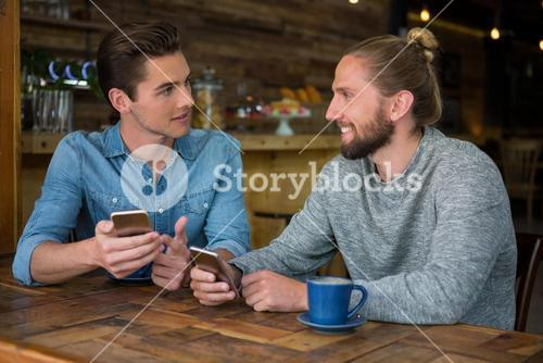 Man talking with friend at table in coffee shop