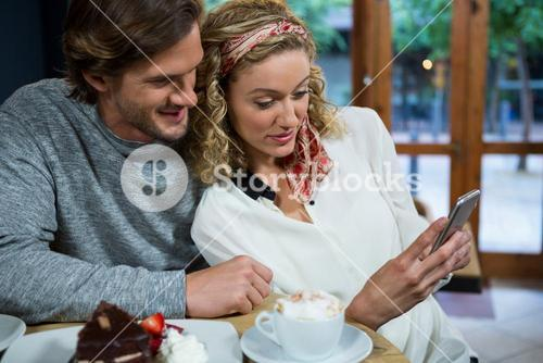 Loving couple using smart phone at table in cafeteria