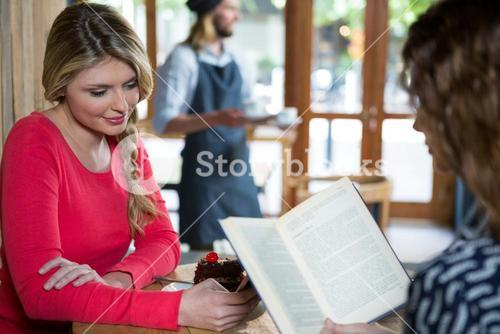Woman using phone while friend reading book in coffee shop