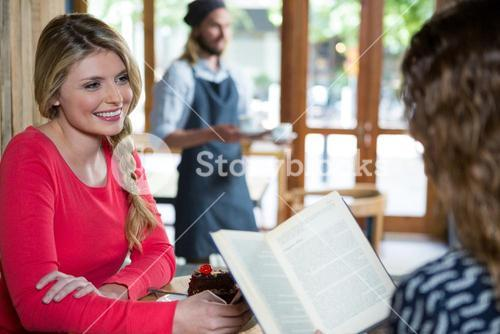 Smiling woman looking at female friend in coffee shop