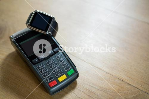Smart watch and credit card reader on table in coffee shop