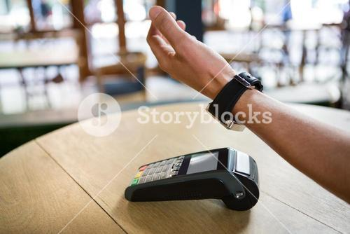 Man using smart watch to express pay in coffee shop