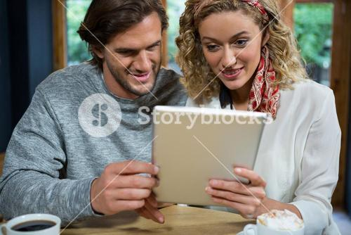 Loving couple using tablet computer at table in cafeteria