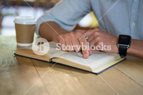 Man reading book at table in coffee shop