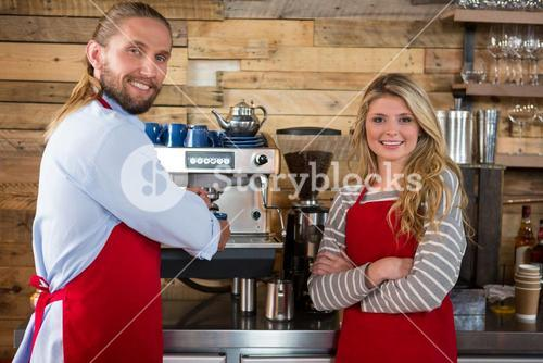 Baristas standing by coffee machine at cafeteria