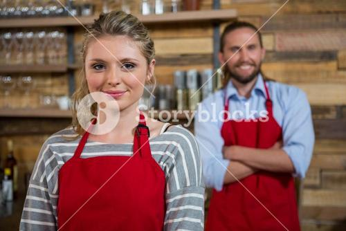 Smiling female barista with male colleague in coffee house