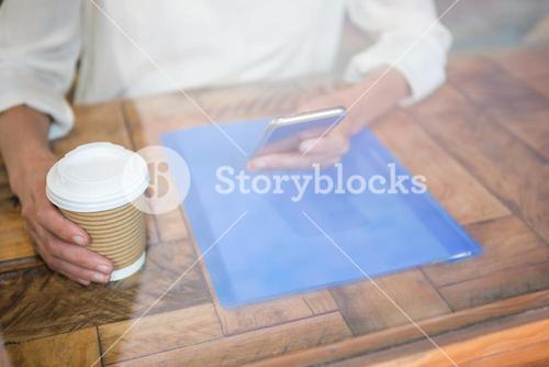 Woman holding coffee cup and smart phone seen through cafe window
