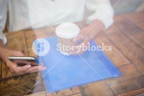 Woman holding coffee cup and mobile phone seen through cafe window