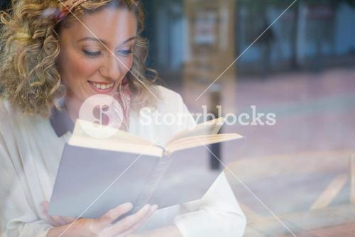 Smiling woman reading book seen through cafe window