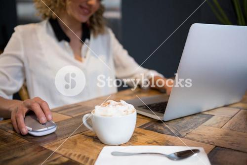 Woman using laptop with coffee on table in cafe