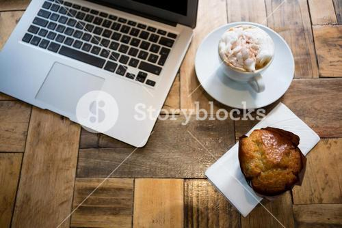 Laptop with coffee and muffin on wooden table in cafe