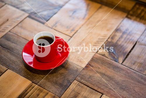 Red cup of espresso served on table