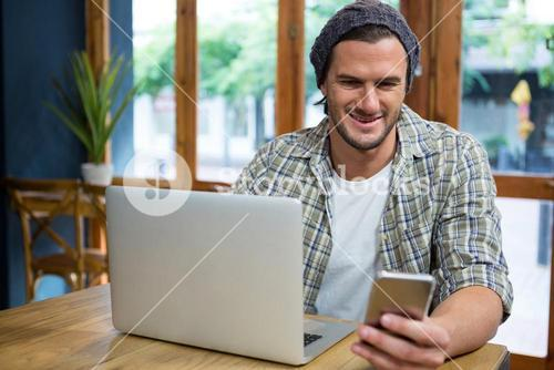 Smiling man using mobile phone and laptop in coffee shop