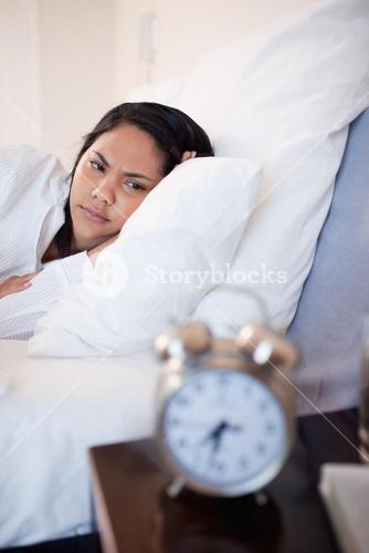 Side view of woman being annoyed by ringing alarm clock